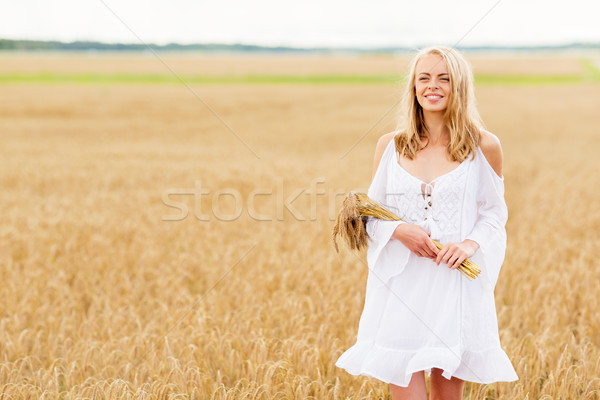 happy young woman with spikelets on cereal field Stock photo © dolgachov