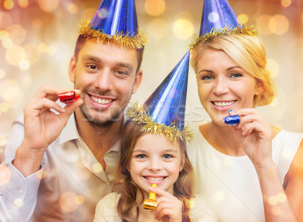 smiling family in blue hats blowing favor horns Stock photo © dolgachov