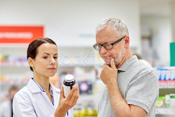 pharmacist showing drug to senior man at pharmacy Stock photo © dolgachov