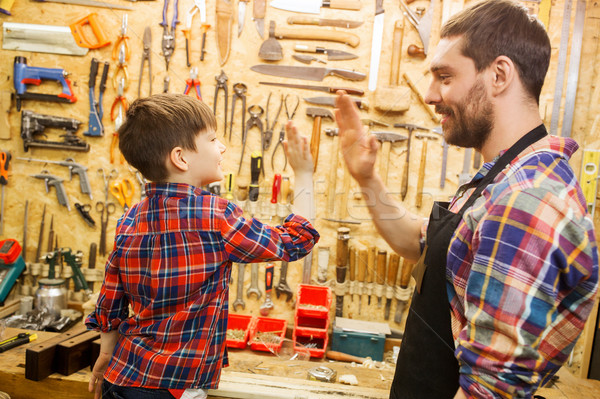 father and little son making high five at workshop Stock photo © dolgachov