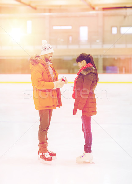 happy couple with engagement ring on skating rink Stock photo © dolgachov