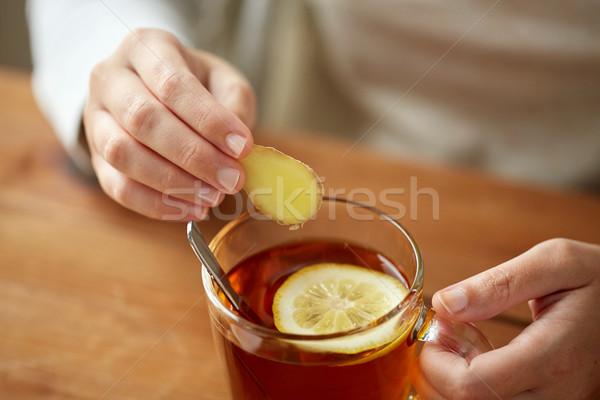 close up of woman adding ginger to tea with lemon Stock photo © dolgachov