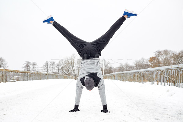 young man doing handstand in winter Stock photo © dolgachov