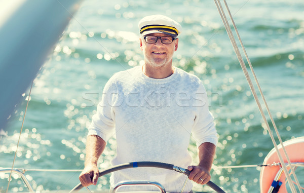 senior man at helm on boat or yacht sailing in sea Stock photo © dolgachov