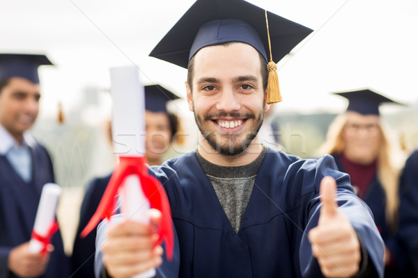 bachelor showing diploma and thumbs up Stock photo © dolgachov