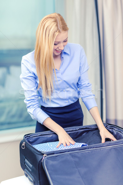 businesswoman packing things in suitcase Stock photo © dolgachov