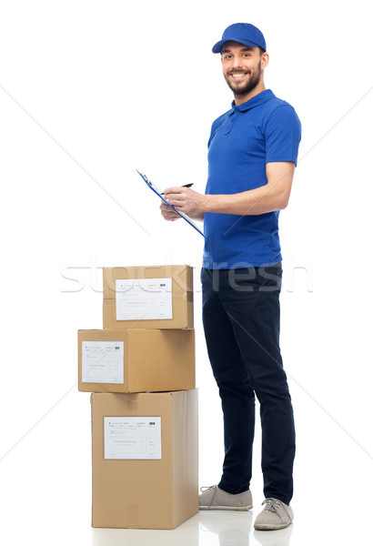 happy delivery man with parcel boxes and clipboard Stock photo © dolgachov