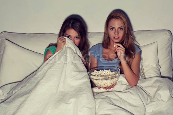 friends with popcorn and watching tv at home Stock photo © dolgachov