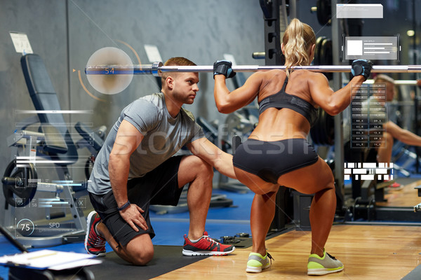 Stock photo: man and woman with barbell flexing muscles in gym
