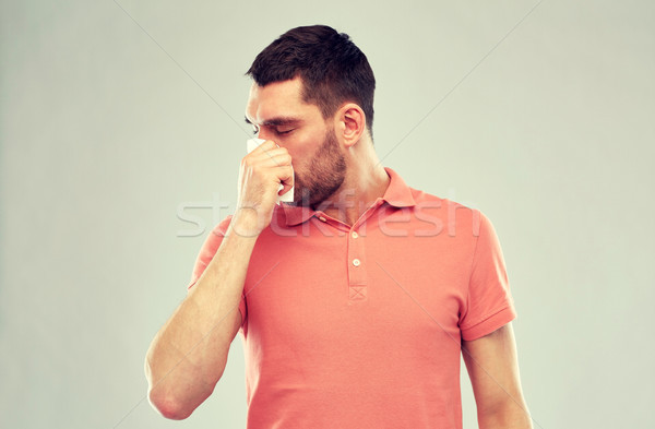 sick man with paper napkin blowing nose Stock photo © dolgachov