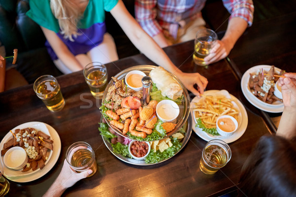 friends eating and drinking at bar or pub Stock photo © dolgachov