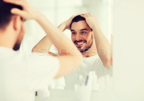 Gelukkig jonge man naar spiegel home badkamer Stockfoto © dolgachov