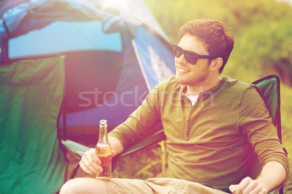 happy young man drinking beer at campsite tent Stock photo © dolgachov
