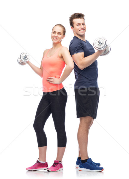Stock photo: sportive man and woman with dumbbells