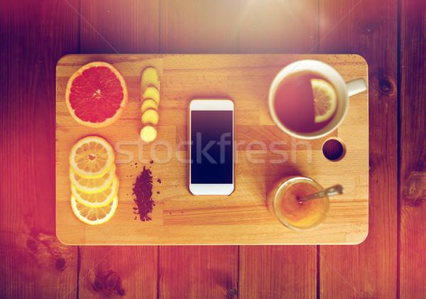 Smartphone kubek cytryny herbaty miodu imbir Zdjęcia stock © dolgachov