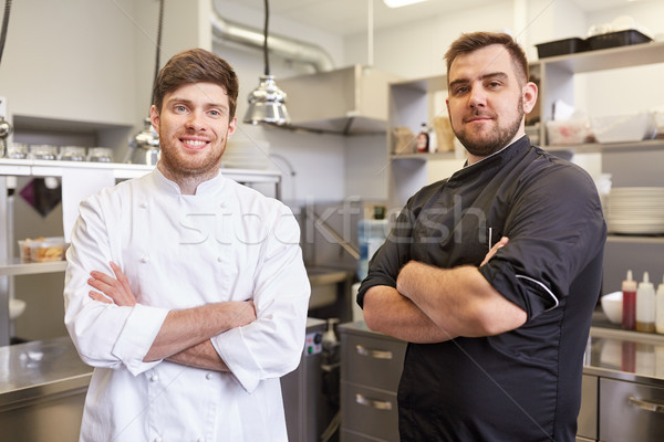 happy smiling chef and cook at restaurant kitchen Stock photo © dolgachov