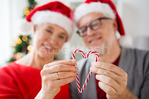 senior couple with heart of christmas candy canes Stock photo © dolgachov