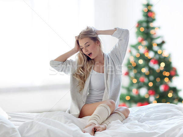 young woman stretching in bed at christmas Stock photo © dolgachov