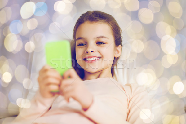 happy girl in bed with smartphone over lights Stock photo © dolgachov