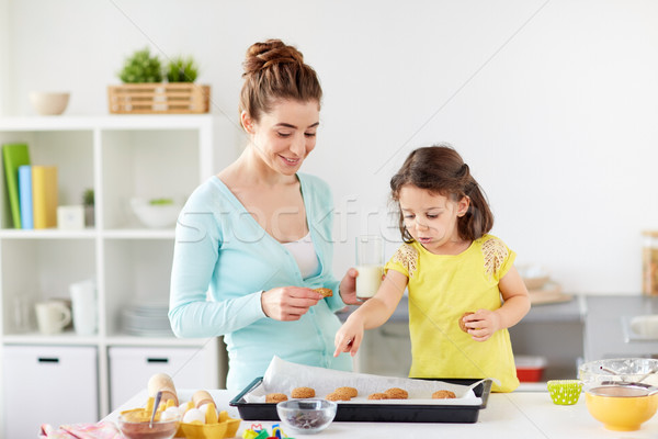 happy mother and daughter eating cookies at home Stock photo © dolgachov