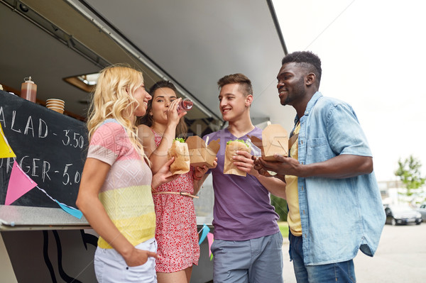 happy friends with drinks eating at food truck Stock photo © dolgachov
