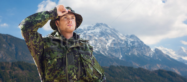 young soldier in military uniform over mountains Stock photo © dolgachov