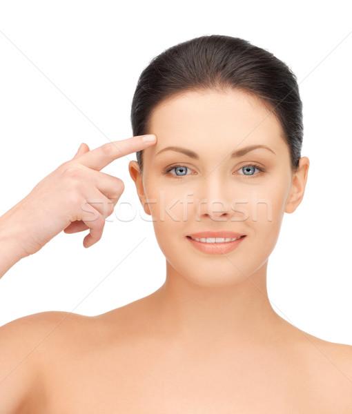 beautiful woman pointing to forehead Stock photo © dolgachov