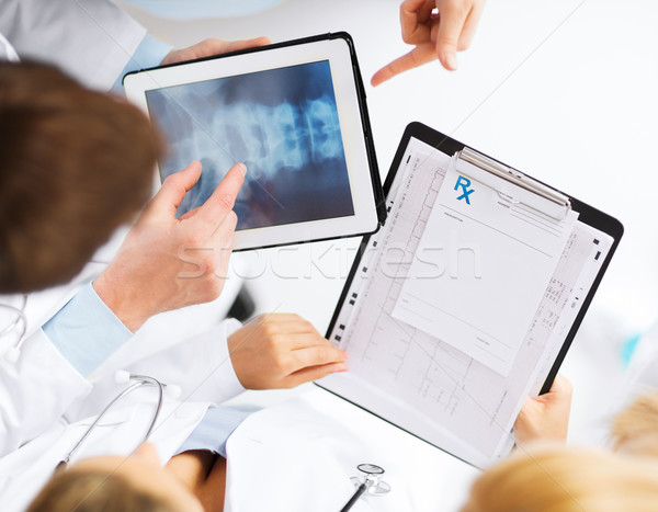 group of doctors looking at x-ray on tablet pc Stock photo © dolgachov