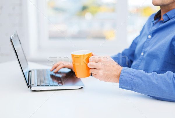 male hand with cup of tea or coffee and laptop Stock photo © dolgachov