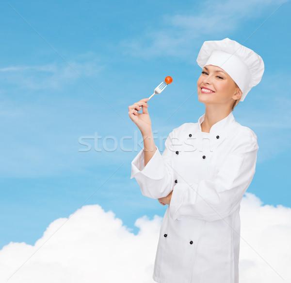 Sorridente feminino chef garfo tomates cozinhar Foto stock © dolgachov