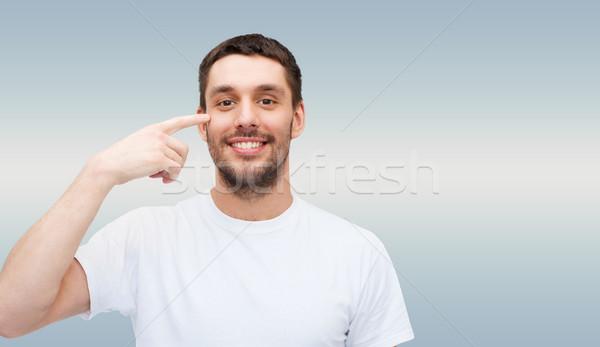 Gülen genç yakışıklı adam işaret gözler sağlık Stok fotoğraf © dolgachov