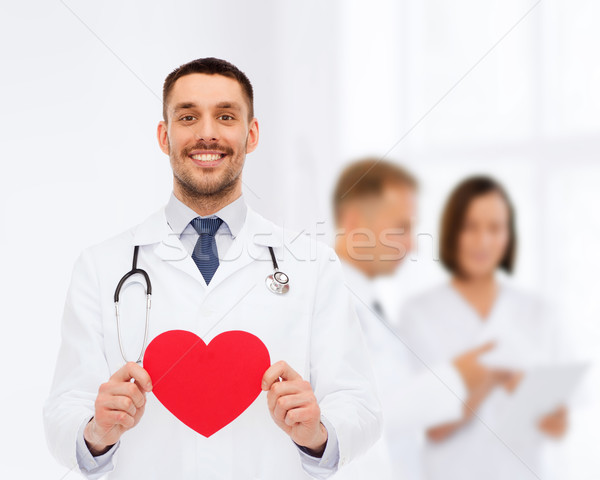 smiling male doctor with red heart Stock photo © dolgachov