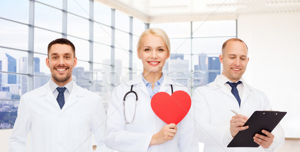 happy young doctors cardiologists with red heart Stock photo © dolgachov