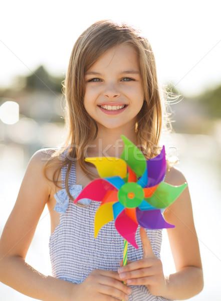 happy girl with colorful pinwheel toy Stock photo © dolgachov