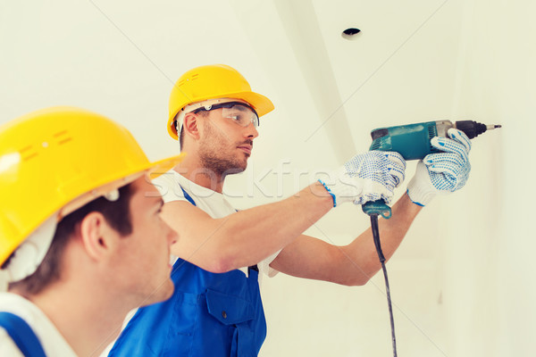 group of builders with drill indoors Stock photo © dolgachov
