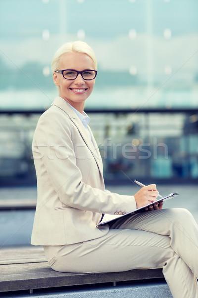Jeunes souriant femme d'affaires notepad extérieur gens d'affaires Photo stock © dolgachov