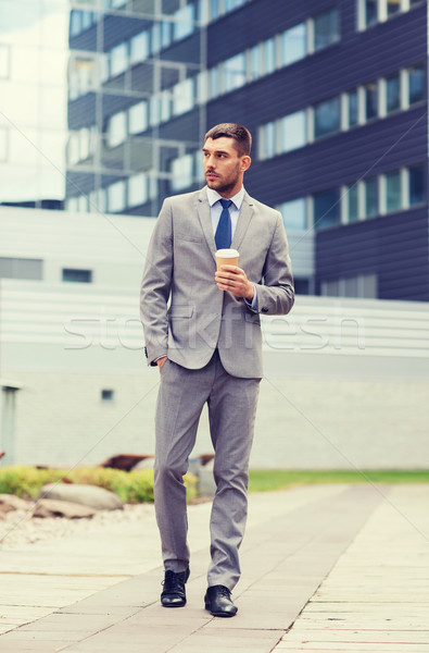 young serious businessman with paper cup outdoors Stock photo © dolgachov