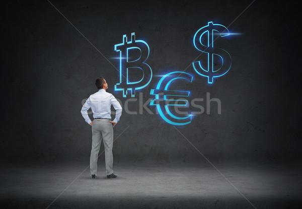 businessman looking at currency symbols Stock photo © dolgachov