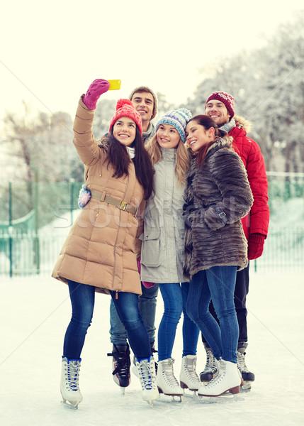 happy friends with smartphone on ice skating rink Stock photo © dolgachov