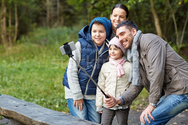 happy family with smartphone selfie stick at camp Stock photo © dolgachov
