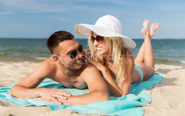 happy couple in swimwear lying on summer beach Stock photo © dolgachov