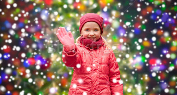 happy little girl waving hand over christmas snow Stock photo © dolgachov