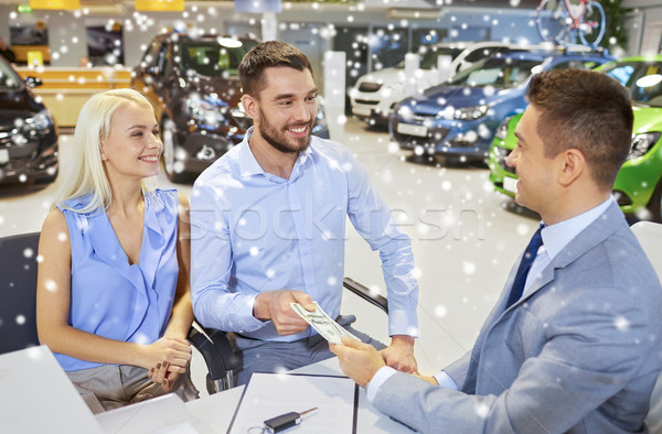 happy couple with money buying car from dealer Stock photo © dolgachov