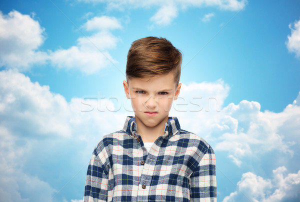 angry boy in checkered shirt over blue sky Stock photo © dolgachov
