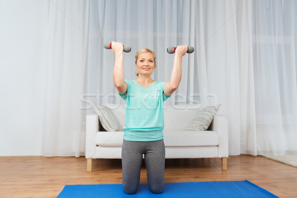 woman exercising with dumbbells on mat at home Stock photo © dolgachov