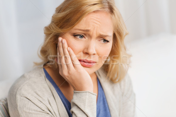 unhappy woman suffering toothache at home Stock photo © dolgachov