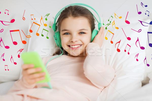 Boldog lány ágy okostelefon fejhallgató emberek gyerekek Stock fotó © dolgachov