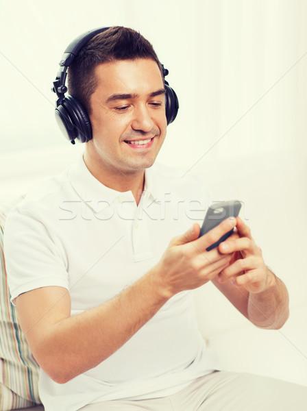 happy man with smartphone and headphones Stock photo © dolgachov