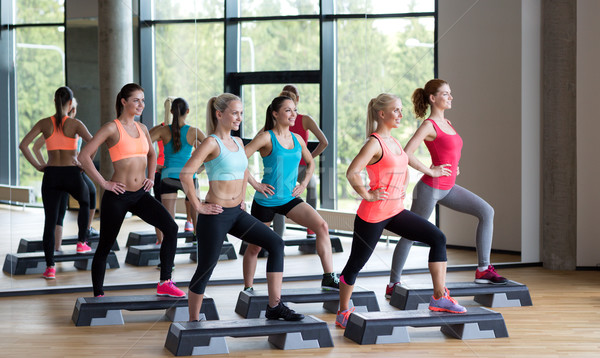 group of women working out with steppers in gym Stock photo © dolgachov