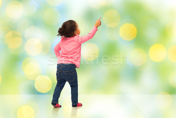african baby girl pointing finger to something Stock photo © dolgachov